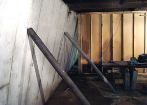 A severely tilting foundation wall propped up by steel beams in Roslindale.