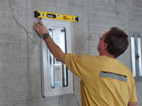 Positioning a wall plate cover on a foundation wall in Quincy.